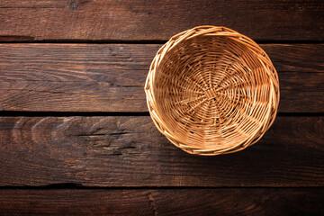 Obraz Empty wicker basket on a wooden background, top view - fototapety do salonu