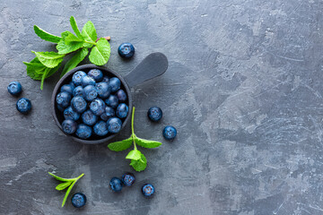 Fresh Blueberries in a bowl on dark background, top view. Juicy wild forest berries, bilberries. Healthy eating or nutrition. Wall mural