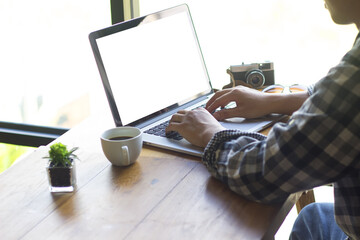 Young man sitting using a laptop on a table by the window.