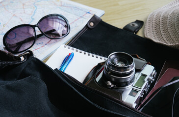 retro camera film, map and Traveler's accessories for the trip on the bag ready for travel, Travel background, Tourist essentials, Top view