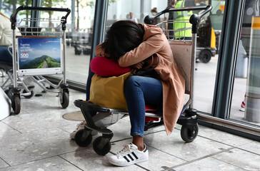 A woman sleeps on a luggage trolley at Heathrow Terminal 5 in London