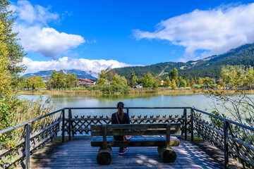 Girl sitting at Lake Wildsee at Seefeld in Tirol, Austria - Europe