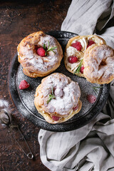 Homemade choux pastry cake Paris Brest with raspberries, almond, sugar powder and rosemary, served on black wooden serving board over dark texture background with textile. French dessert. Top view
