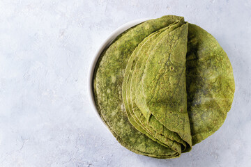 Stack of empty green spinach matcha tortillas in terracotta plate over gray texture background. Flat lay with copy space