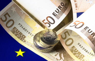 European cash money. Rolled fifty euro bills on the european community flag background. Heap of euro coins on the bills Macro image.