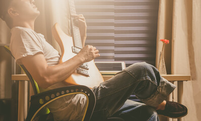 asian man playing electric guitar for relaxation in the room