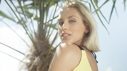Young beautiful blonde girl posing on tropical beach.