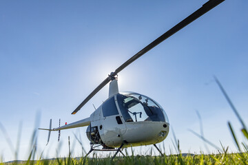 Poster Helicopter Small Robinson R22 light utility helicopter parked on grass airport. One of the world's most popular light helicopters with twin blades and a single engine
