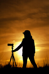 Female photographer with camera at sunsetlight