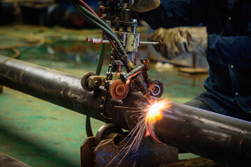 Worker cutting steel pipe with acetylene welding cutting torch and bright sparks in steel construction industry.