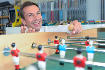 Man puting ball onto table football game