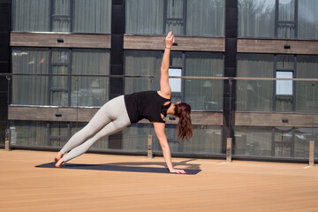 sport woman doing stretching yoga exercise on hotel roof with wooden floor stand on yoga mat
