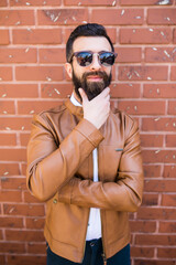 Portrait of a brutal bearded man on brick wall background. Young stylish hipster posing in the street.