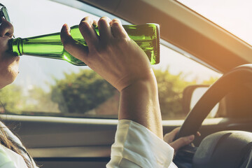 Woman drinking beer while driving a car