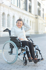 Senior lady in wheelchair in urban setting