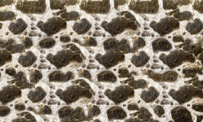 Textured stone walls built of large rough stones held together by dark lumps of white cement limestone
