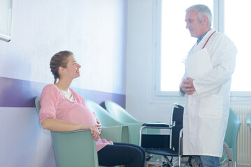 Doctor greeting pregnant woman in waiting room