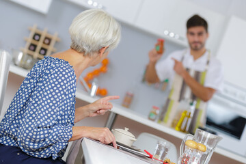 Man checking condiment for woman's meal