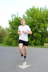 молодой спортсмен бежит по беговой асфальтированной дорожке в парке летом