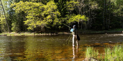 Fly fisherman using flyfishing rod in a beautiful river in spring