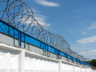 Barbed wire on the wall against the blue sky