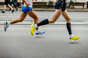 legs of two men runners athletes running on city street
