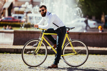 Handsome hipster young bearded man looking at camera while sitting on his bicycle outdoors near fountains