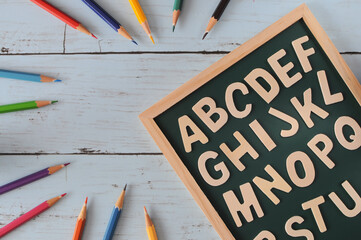Alphabet letters on blackboard with colored pencil, education concept and back to school idea