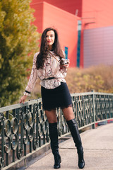 Beautiful tall girl with long curly hair sexy out on sunny day. Taking pictures with vintage camera dressed in knee-high boots, mini skirt and fishnet stockings exposing her skin.