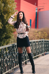 Sweet girl dressed in feminine outfit with pink blouse, mini skirt and fishnet stockings holding vintage camera. Trying to take pictures draws people's attention to her to photograph them