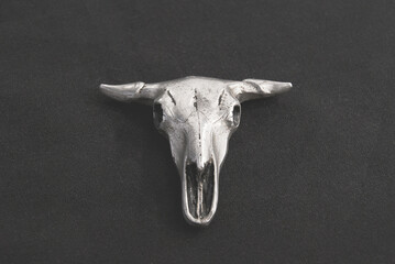 Pendant in the form of a bull's skull on a black background