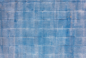 Distressed blue streaked cinder block wall background.