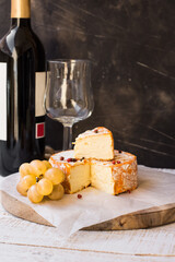 French munster cheese with orange rind, red pepper corns, white grapes cut off slice, wine bottle and glass, copyspace