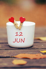 June 12th. Day 12 of month, color calendar on morning coffee cup at nature background. Summer concept. Empty space for text