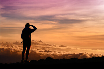 Tourist admiring breathtaking sunset views from the Mauna Kea, a dormant volcano on the island of Hawaii
