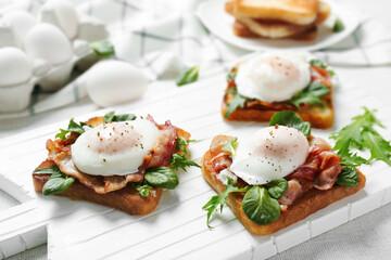 Tasty eggs Benedict on cutting board