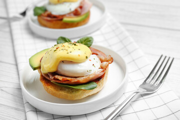 Plate with tasty egg Benedict and fork on table