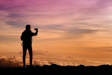 Tourist admiring breathtaking sunset views from the Mauna Kea, a dormant volcano on the island of Hawaii