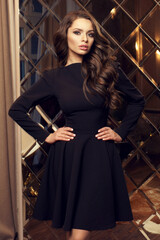 Stunning beautiful female model wearing black cocktail dress, standing and posing in luxury interior with large mirror. Fashion portrait.