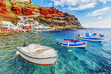 Fishing boats over clear turquoise water of Aegean sea at Old port Amoudi of Oia village at Santorini island, Greece Fototapete