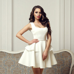Young elegant woman in white dress with circular skirt standing in bright interior against sofa and white wall and looking at you.