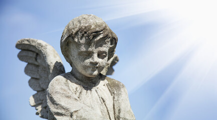 Guardian angel statue in sunlight as a symbol of strength, truth and faith.