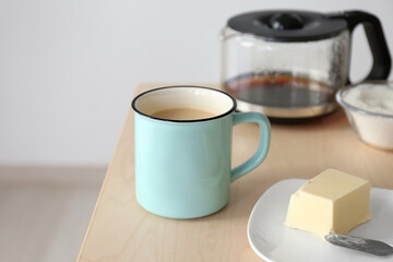 Cup of coffee with butter on table