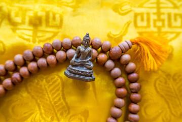 Buddhafigur mit Gebetskette auf gelben Seidentuch