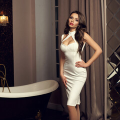 Young beautiful sexy brunette woman with long brown curly hair posing in white halter dress in luxury interior with mirror wall and bath