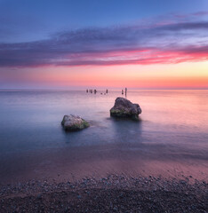 Wall Mural - Amazing sunrise at the sea. Beautiful landscape with blue water, stones and colorful sky with red and orange clouds in summer morning. Seascape. Tranquil scene. Nature background