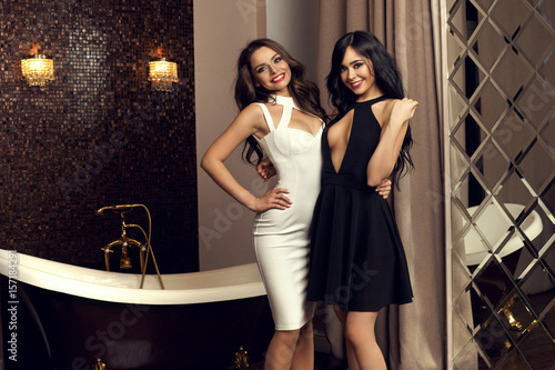 Two Sexy Girls Posing In Luxury Interior With Mirror Wall And Bath