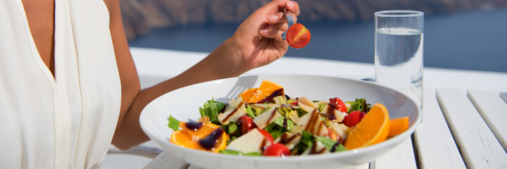Healthy woman eating salad banner crop of diet meal at restaurant table. Closeup of plate on outdoor cafe terrace plate, luxury dining.