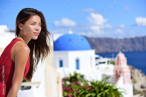 Wall mural Santorini woman Europe cruise travel vacation. Tourist Asian beauty girl relaxing looking at view of three blue domes, Oia island, Greece, famous Europe cruise destination.