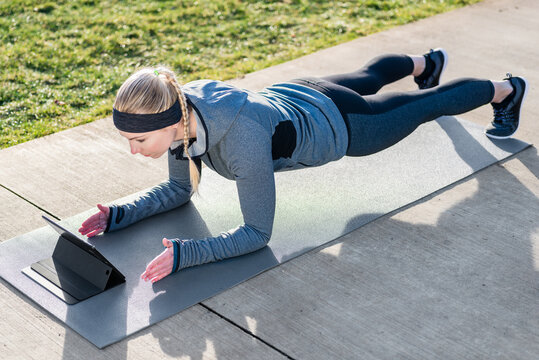 High-angle view of fit young woman watching a motivational video on tablet PC while exercising the plank on mat outdoors in the park